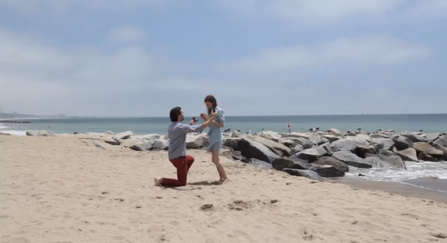 Guy on beach videoing his proposal